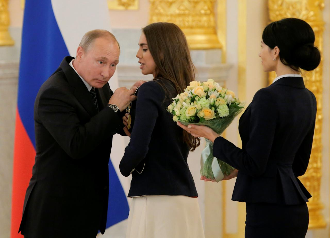 Russian President Vladimir Putin awards rhythmic gymnast Margarita Mamun during a ceremony for Russian Olympic medallists returning home from the 2016 Rio Olympics, at the Kremlin in Moscow, Russia August 25, 2016. REUTERS/Maxim Shemetov