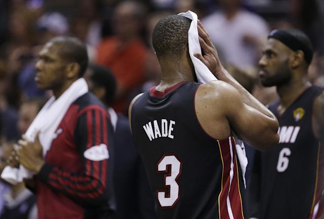 Miami Heat guard Dwyane Wade (3) wipes his face in the final moments at Game 5 of the NBA basketball finals on Sunday, June 15, 2014, in San Antonio. The San Antonio Spurs won the NBA championship 104-87. (AP Photo/David J. Phillip)