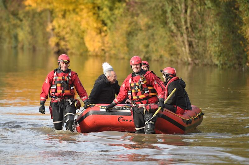 Members of West Midlands Fire Service help to rescue residents from floodwater near Fishlake (PA)