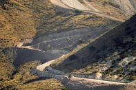 """FILE - A pathway cleared by explosives to make way for border wall construction separates Mexico, right, and the United States, Wednesday, Dec. 9, 2020, in Guadalupe Canyon, Ariz. President Biden on Wednesday ordered a """"pause"""" on all wall construction within a week, one of 17 executive edicts issued on his first day in office, including six dealing with immigration. The order leaves projects across the border unfinished and under contract after Trump worked feverishly last year to reach 450 miles, a goal he announced was achieved eight days before leaving office. (AP Photo/Matt York)"""