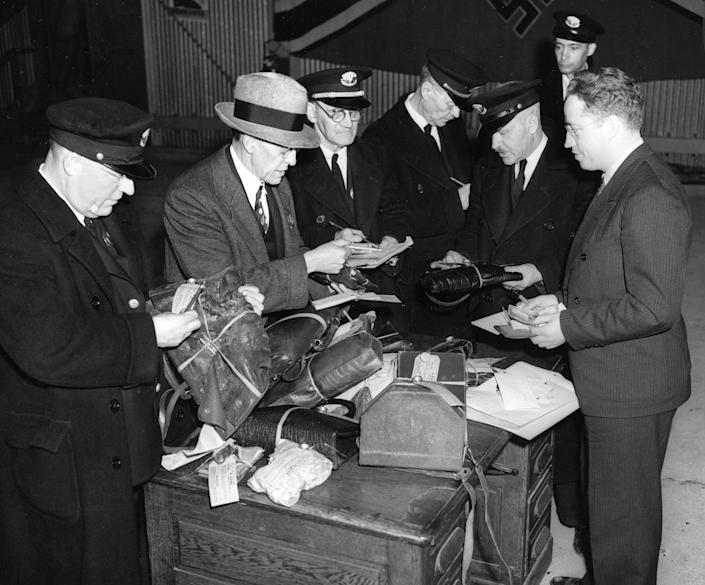 <p>Customs officers search through baggage items salvaged in the Hindenburg explosion in Lakehurst, N.J., May 6, 1937. (AP Photo) </p>
