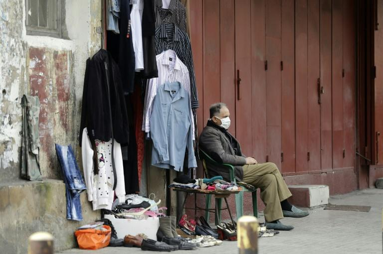 A street vendor sits with his face covered with a protective mask outside a closed shop in the Lebanese capital Beirut (AFP Photo/JOSEPH EID)