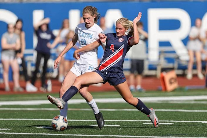 Providence Day defender Lauren Jensen (4) battles Latin forward Mary Schleusner in the first half in Charlotte, N.C., Saturday, May 15, 2021.