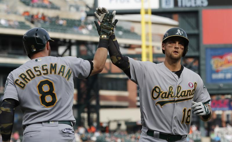 Oakland Athletics' Chad Pinder (18) is greeted at home plate by teammate Robbie Grossman after hitting a solo home run during the seventh inning of a baseball game against the Detroit Tigers, Saturday, May 18, 2019, in Detroit. (AP Photo/Carlos Osorio)