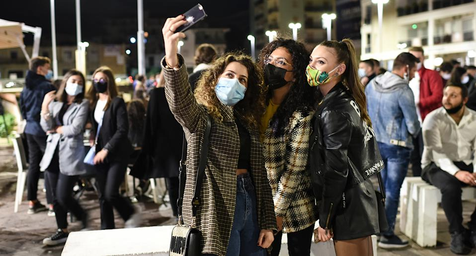 Three women take a selfie in a busy Italian street.