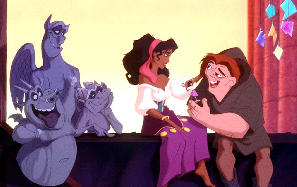 """Quasimodo, the reclusive bell ringer of Notre Dame (R) meets Esmeralda, a Gypsy dancer as gargoyle plas-Victor, Hugo and Laverne look on in a scene from Walt Disney Pictures' new musical animated film """"The Hunchback of Notre Dame."""" The film premieres in the United States June 19"""