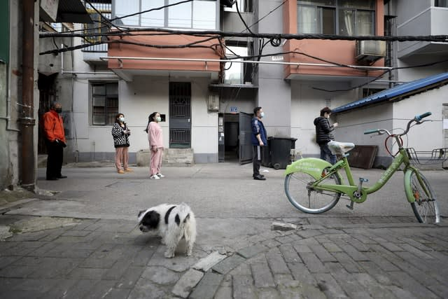 People stand in a spaced line as they wait to buy pork at the entrance gate of a closed residential community in Wuhan in central China's Hubei Province