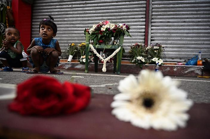 Children sit next to flowers left by mourners near St. Anthony's Shrine in Colombo, two days after a series of bomb blasts killed more than 350 people (AFP Photo/Jewel SAMAD)