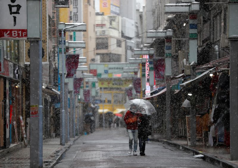 A couple wearing protective face masks walks on a nearly empty street in a snow fall during a coronavirus disease outbreak in Tokyo