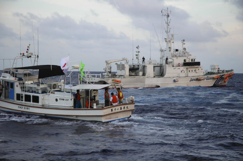 Japanese Coast Guard vessel, right, sails alongside Japanese activists' fishing boat, left, near a group of disputed islands called Diaoyu by China and Senkaku by Japan, early Sunday, Aug. 18, 2013. Nearly two dozen Japanese nationalist activists and fishermen have sailed to a small group of islands at the center of a territorial dispute with China. They were closely monitored by Japan's Coast Guard, but there were no Chinese patrols in the area and no incidents were reported. (AP Photo/Emily Wang)