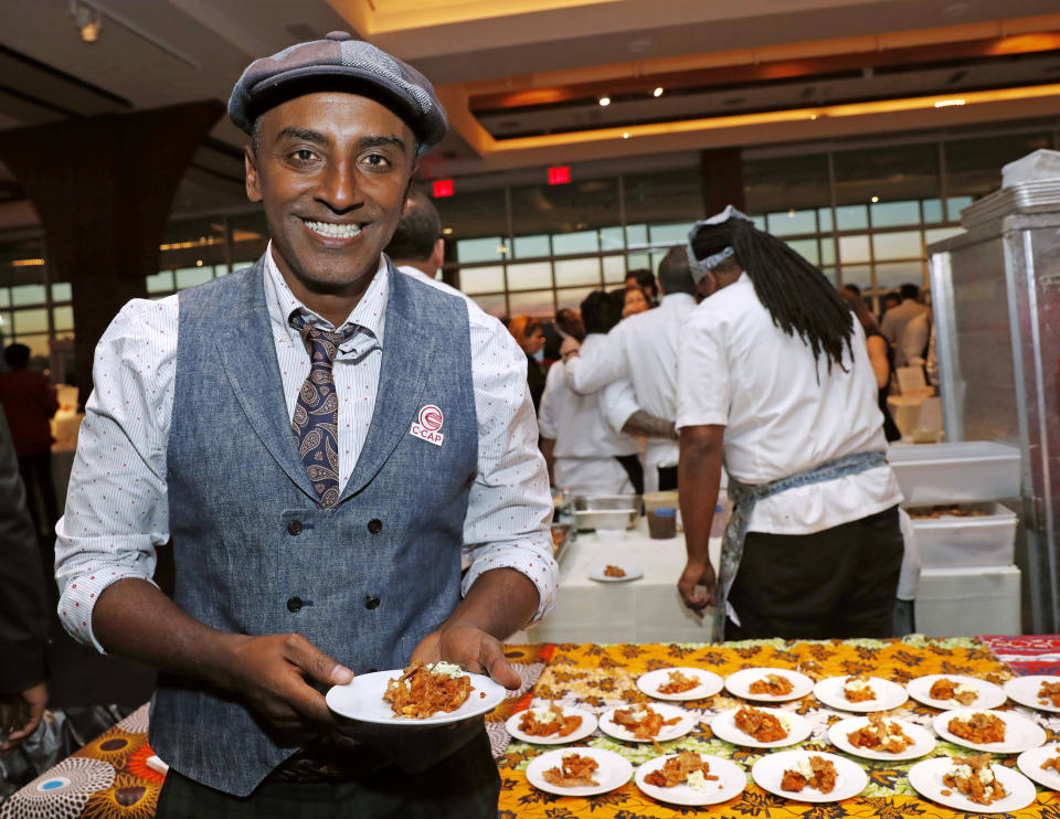 """Chef Marcus Samuelsson, who is Ethiopian, but was raised in Sweden, founder of Red Rooster Harlem and more than a dozen other restaurants, holds a tasting plate of Dorowat """"lasagna,"""" with injera (Ethiopian flatbread), ayib (Ethiopian cheese), rosemary, and crispy skin, during the C-CAP (Careers through Culinary Arts Program) annual benefit, Tuesday, Feb. 27, 2018, in New York. (AP Photo/Kathy Willens)"""