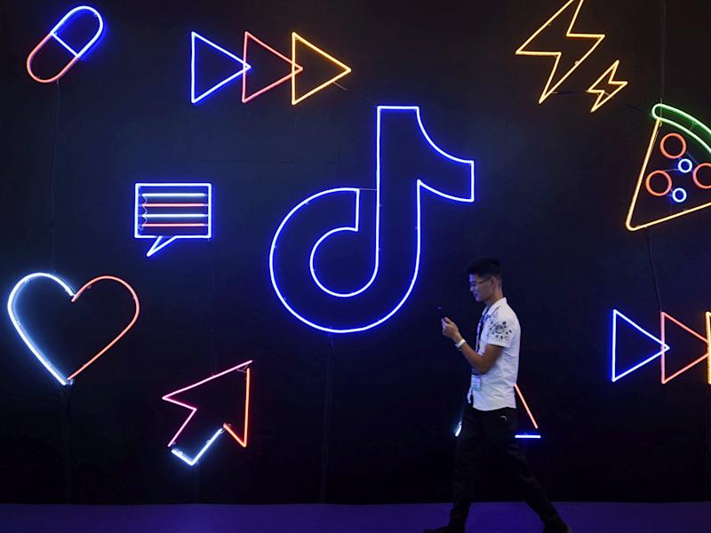 Man walks past a sign of ByteDance's app TikTok, known locally as Douyin, at an expo in Hangzhou