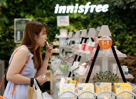FILE PHOTO:  A customer tries a lipstick at a shop of Innisfree, Amorepacific's budget brand in central Seoul, South Korea