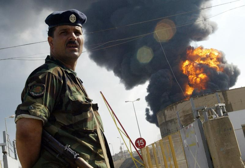 A Lebanese soldier stands guard in front flaming fuel tanks at the Beirut International airport, after an Israeli air strike on July 14, 2006 (AFP Photo/Ramzi Haidar)