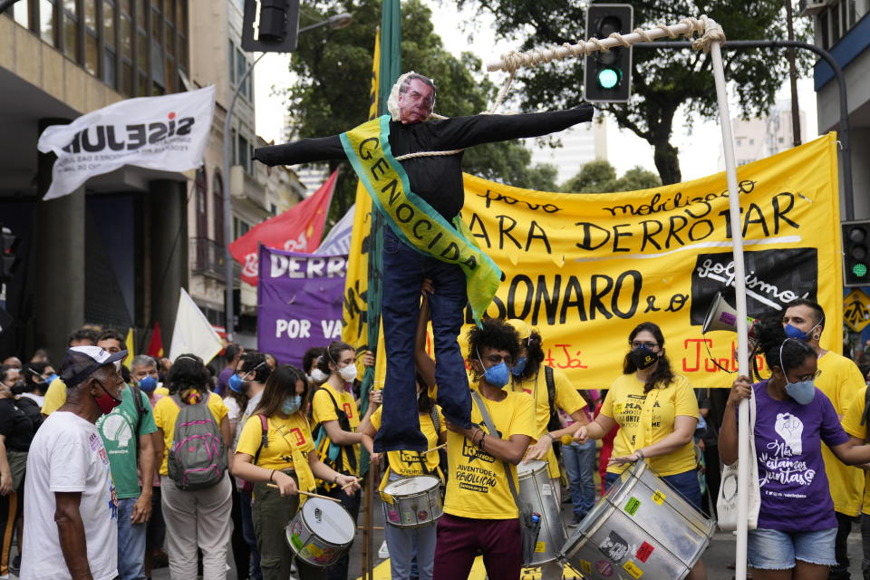 """A protester holds an effigy of Brazilian President Jair Bolsonaro that reads in Portuguese """"Genocide"""" during a protest against the president's handling of the COVID-19 pandemic, the economy and corruption, on Independence Day in Rio de Janeiro, Brazil, Tuesday, Sept. 7, 2021. (AP Photo/Silvia Izquierdo)"""
