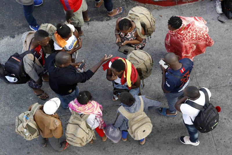 People gather as they wait to apply for asylum in the United States along the border, Tuesday, July 16, 2019, in Tijuana, Mexico. Dozens of immigrants lined up Tuesday at a major Mexico border crossing, waiting to learn how the Trump administration's plans to end most asylum protections would affect their hopes of taking refuge in the United States. (AP Photo/Gregory Bull)