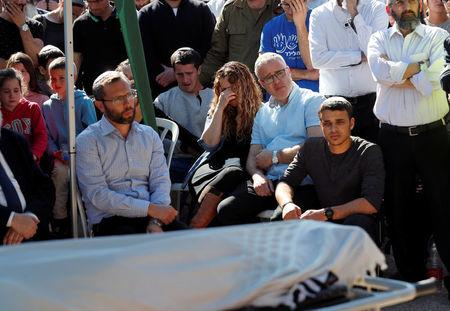 Relatives and friends mourn as they sit next to the body of Israeli rabbi Achiad Ettinger, wrapped in a Jewish prayer shawl, during his funeral, in the Jewish settlement of Eli in the Israeli-occupied West Bank