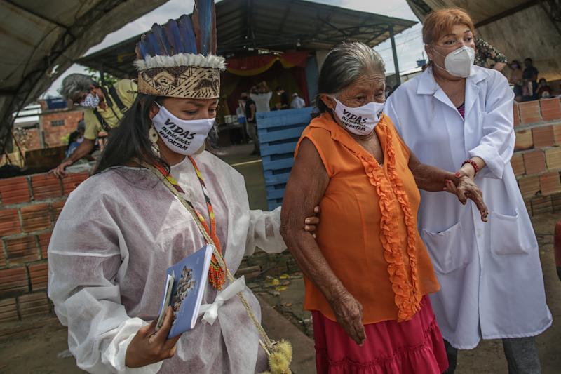 MANAUS, BRAZIL - MAY 21.: Indigenous nurses wearing protective masks take an elderly woman to make testing at Parque das Tribos community, on May 21 2020 in Manaus, Brazil. Medical teams from Healths Secretary of Manaus area performing vaccination against flu and testing to detect coronavirus (COVID-19) infections on indigenous communities. (Photo by Andre Coelho/Getty Images)