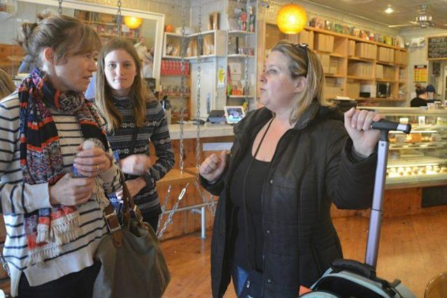 Lori Pickhardt (right) is showing two tourists directions at the end of the food tour.