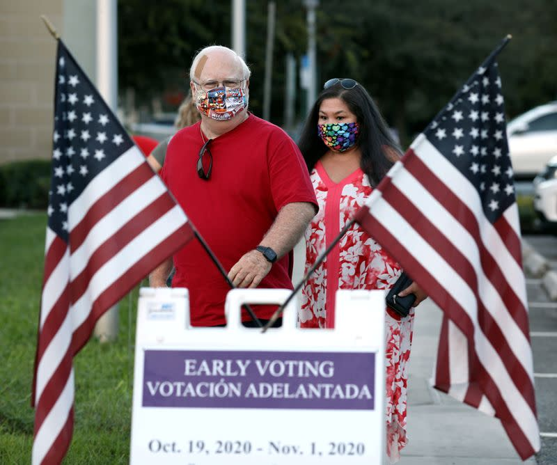 FILE PHOTO: People line up to cast ballots during early voting session in Celebration, Florida
