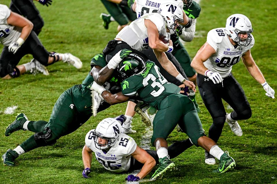 Michigan State's Naquan Jones, left, and Antjuan Simmons, right, tackle Northwestern's Peyton Ramsey during the third quarter on Saturday, Nov. 28, 2020, at Spartan Stadium in East Lansing.