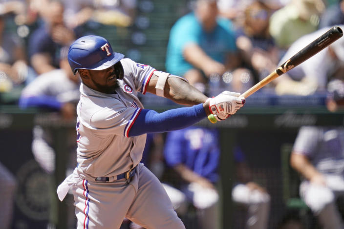Texas Rangers' Adolis Garcia singles in a run against the Seattle Mariners in the sixth inning of a baseball game Sunday, July 4, 2021, in Seattle. (AP Photo/Elaine Thompson)