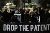 Global Justice campaigners carry fake coffins to highlight the number of COVID-19 deaths globally, in London, Tuesday, Oct. 12, 2021. Britain is taking part in a World Trade Organisation intellectual property meeting to boost the number of vaccinations world wide. The campaigners want large pharmaceuticals companies to drop patents on COVID-19 drugs to allow poorer nations to vaccinate their populations. (AP Photo/Alastair Grant)
