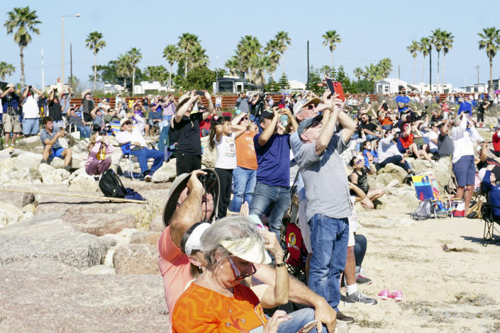 Spectators at Isla Blanca Park on South Padre Island, Texas, look up for a glimpse of SpaceX's bullet-shaped Starship prototype during a test launch, Tuesday, Feb. 2, 2021. The test flight ended in a fiery crash when the Starship attempted to land. (Miguel Roberts/The Brownsville Herald via AP)