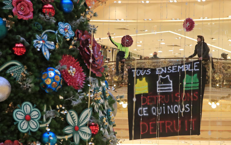 Yellow vest demonstrators shout after they unfurl a giant banner that reads, 'all together, let us destroy what is destroying us' as they stage a protest at the Galeries Lafayette shopping mall in Paris, Sunday, Nov. 17, 2019. Yellow vest protesters staged new actions Sunday across France to mark the birth last year of their movement for economic justice, one day after scuffles between Paris police and activists marred the anniversary. (AP Photo/Michel Euler)