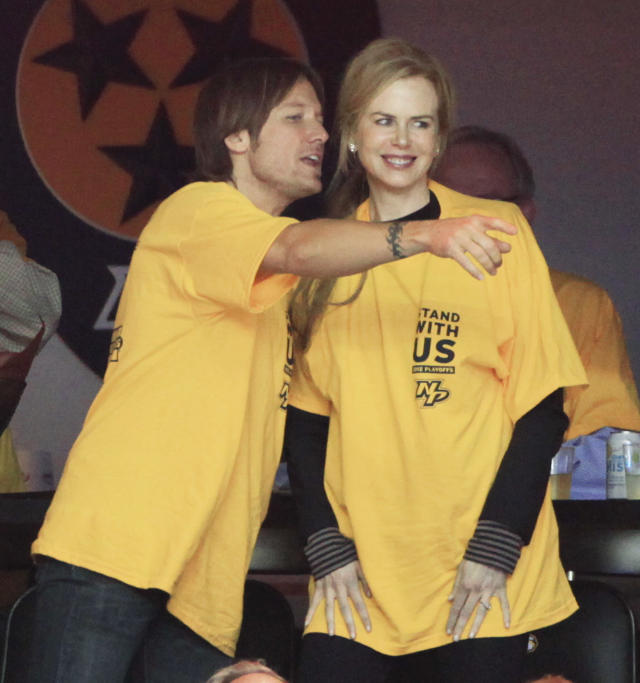 Singer Keith Urban, left, and wife, actress Nicole Kidman watch the Nashville Predators play the Detroit Red Wings in the first period of Game 5 of a first-round NHL hockey playoff series on Friday, April 20, 2012, in Nashville, Tenn. (AP Photo/Mark Humphrey)
