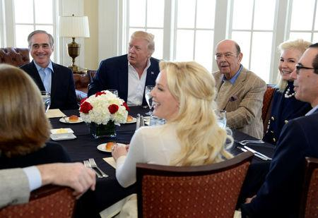 President Donald Trump makes remarks to the press as he sits down for a working lunch with members of his cabinet and their spouses, including Veteran's Administration Secretary David Shulkin (L), Labor Secretary Wilbur Ross (3rd R) and Treasury Secretary Steven Mnuchin (R), sitting with his fiance Louise Linton (foreground), at Trump National Golf Club, Potomac Falls,Virginia, in suburban Washington, U.S., March 11, 2017.           REUTERS/Mike Theiler