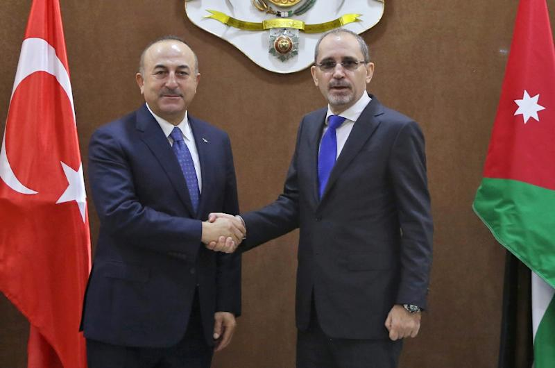 Turkish Foreign Minister Mevlut Cavusoglu (L) is greeted by his Jordanian counterpart Ayman Safadi upon his arrival in Amman on February 19, 2018 (AFP Photo/Khalil MAZRAAWI)