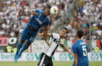 Juventus' Alex Sandro, left, jumps for the ball with Parma's Roberto Inglese during the Serie A soccer match between Parma and Juventus at the Tardini stadium, in Parma, Italy, Saturday, Aug. 24, 2019. (AP Photo/Antonio Calanni)