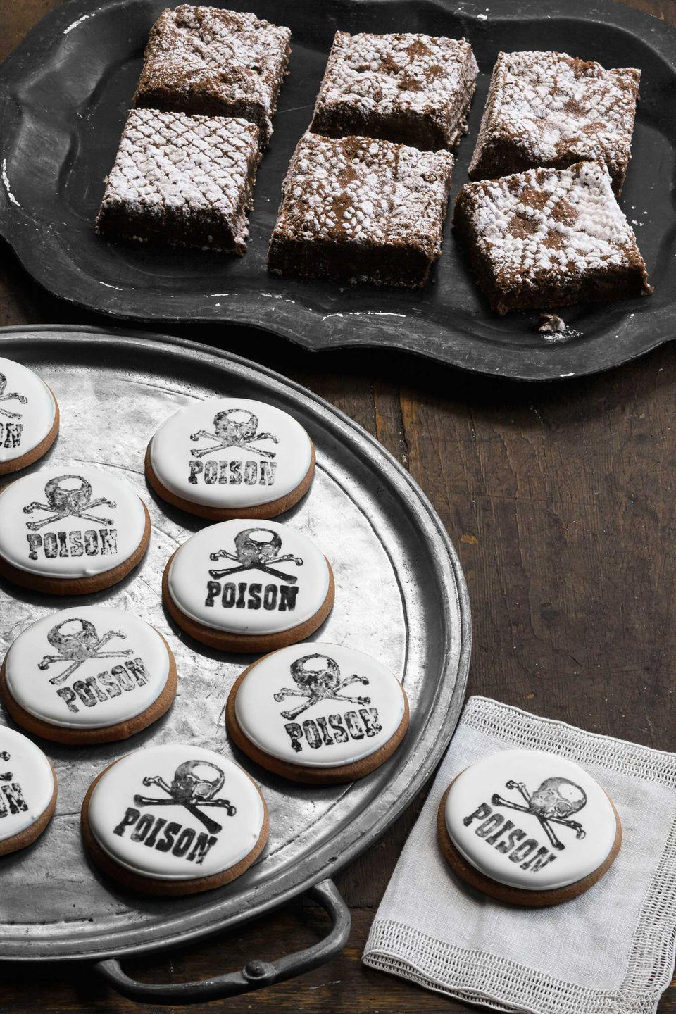 """<p>Tarting up these desserts is frighteningly simple. To decorate brownies, lay a swatch of lace on one of the treats. Sift confectioners' sugar over the top, then carefully remove the lace; repeat for remaining brownies. </p><p>For the """"poison"""" cookies, frost sugar cookies with white royal icing, allowing it to set overnight. Next, put a small amount of black gel paste in a shallow dish, and lay two stacked paper towels atop the gel paste. Press a skull-and-crossbones rubber stamp onto the towels and then onto one iced cookie; repeat the process for your entire batch.</p><p><strong><a href=""""https://www.countryliving.com/food-drinks/recipes/a34963/basic-sugar-cookie-dough-recipe-wdy1214/"""" rel=""""nofollow noopener"""" target=""""_blank"""" data-ylk=""""slk:Get a basic sugar cookie recipe"""" class=""""link rapid-noclick-resp"""">Get a basic sugar cookie recipe</a>.</strong> </p><p><strong><a href=""""https://www.countryliving.com/food-drinks/recipes/a1757/royal-icing-3883/"""" rel=""""nofollow noopener"""" target=""""_blank"""" data-ylk=""""slk:Get the recipe for royal icing"""" class=""""link rapid-noclick-resp"""">Get the recipe for royal icing</a>.</strong></p>"""