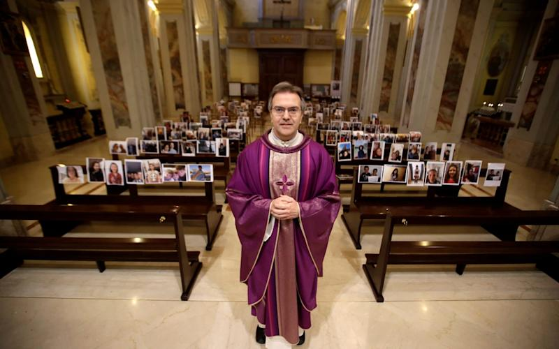 Don Giuseppe Corbari, poses in front of selfies he was sent by parishioners - AP Photo/Luca Bruno
