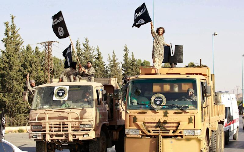 Militant Islamist fighters wave flags as they take part in a military parade along the streets of Raqqa - Reuters