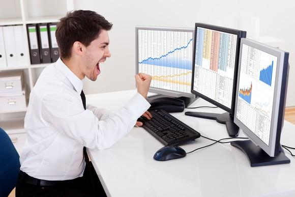 An investor pumping his right fist in front of computer monitors showing rising stock charts.