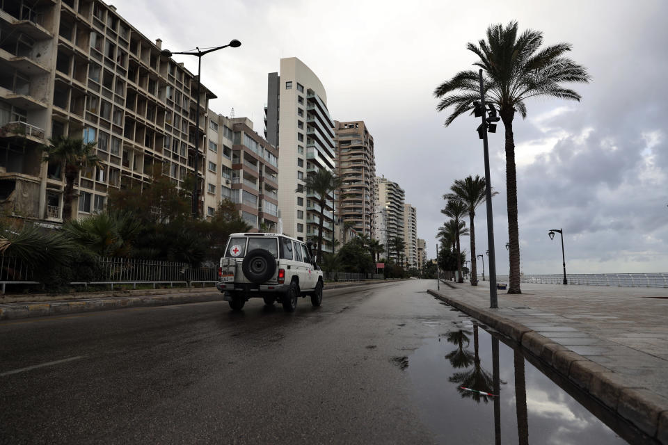 A Red Cross vehicle drives along the empty waterfront promenade as the country starts a new lockdown, in Beirut, Lebanon, Thursday, Jan. 14, 2021. Lebanese authorities began enforcing an 11-day nationwide shutdown and round the clock curfew Thursday, hoping to limit the spread of coronavirus infections spinning out of control after the holiday period. (AP Photo/Bilal Hussein)