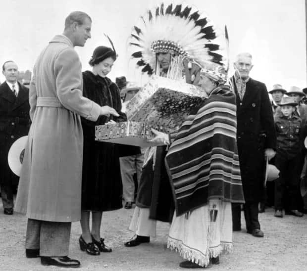 FILE - In this Oct. 18, 1951 file photo, Britain's Princess Elizabeth and her husband the Duke of Edinburgh, holding his 10-gallon hat, receive a gift from a chief and his wife during The Calgary Stampede at Calgary.  (The Associated Press - image credit)