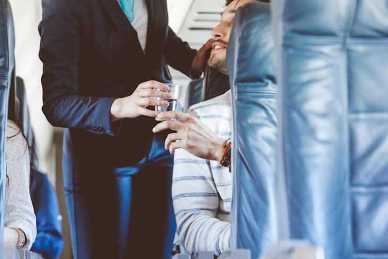 Air stewardess serving water inside an airplane, close up of hands, unrecognizable person.