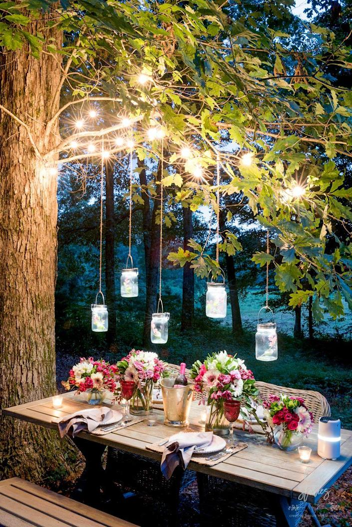 """<p>Pairing simple string lights with illuminated jars makes for a breathtaking display. Who wouldn't want to pull up a seat at this outdoor dinner table?!</p><p><strong>See more at <a href=""""https://www.homestoriesatoz.com/decorating/outdoor-table-setting-tips-products-to-help-create-a-gorgeous-outdoor-tablescape.html"""" rel=""""nofollow noopener"""" target=""""_blank"""" data-ylk=""""slk:Home Stories A to Z"""" class=""""link rapid-noclick-resp"""">Home Stories A to Z</a>.</strong></p><p><strong><a class=""""link rapid-noclick-resp"""" href=""""https://www.amazon.com/Lantern-Firefly-Hangers-Included-Lanterns/dp/B072BFN2CD?tag=syn-yahoo-20&ascsubtag=%5Bartid%7C10050.g.3404%5Bsrc%7Cyahoo-us"""" rel=""""nofollow noopener"""" target=""""_blank"""" data-ylk=""""slk:SHOP JARS"""">SHOP JARS</a><br></strong></p>"""