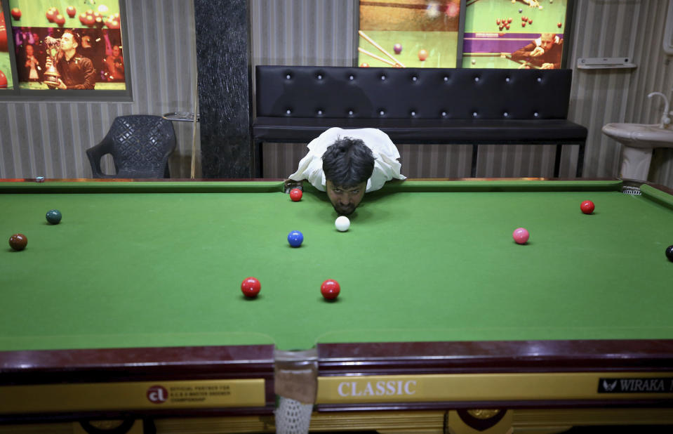 Mohammad Ikram plays snooker with his chin at a local snooker club in Samundri town, Pakistan, Sunday, Oct. 25, 2020. Ikram, 32, was born without arms, but everyone simply admires his snooker skills when he hits the cue ball with his chin and pots a colored ball on a snooker table. He lives in a remote rural town of Punjab province and his physical disability doesn't come in his way to fulfill his childhood dream of playing the game of snooker. (AP Photo/Anjum Naveed)