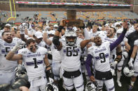 FILE - In this Nov. 30, 2019, file photo, Northwestern celebrates with the Land Of Lincoln trophy after beating Illinois 29-10 in an NCAA college football game in Champaign, Ill. Big Ten is going to give fall football a shot after all. Less than five weeks after pushing football and other fall sports to spring in the name of player safety during the pandemic, the conference changed course Wednesday, Sept. 16, 2020, and said it plans to begin its season the weekend of Oct. 23-24. (AP Photo/Charles Rex Arbogast, File)
