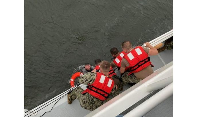 Crew members of the Coast Guard Cutter Glenn Harris pull a man from the water after a commercial lift vessel capsized in a storm in the Gulf of Mexico off Louisiana on April 13, 2021. U.S. Coast Guard Photo courtesy of Coast Guard Cutter Glenn Harris/Handout via REUTERS / Credit: U.S. Coast Guard Photo courtesy of Coast Guard Cutter Glenn Harris / Handout via REUTERS