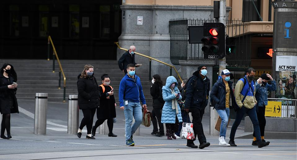 A small crowd of people pictured walking along a Melbourne street, some wearing masks. Source: AAP