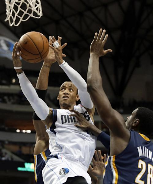 Dallas Mavericks point guard Monta Ellis, center, drives past Indiana Pacers' David West, rear, and Ian Mahinmi, right, for a shot attempt in the first half of a preseason NBA basketball game, Friday, Oct. 25, 2013, in Dallas. (AP Photo/Tony Gutierrez)