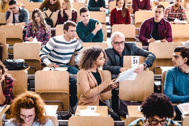 Mature professor assisting his female student with a lecture in a textbook at lecture hall. (Photo: skynesher via Getty Images)