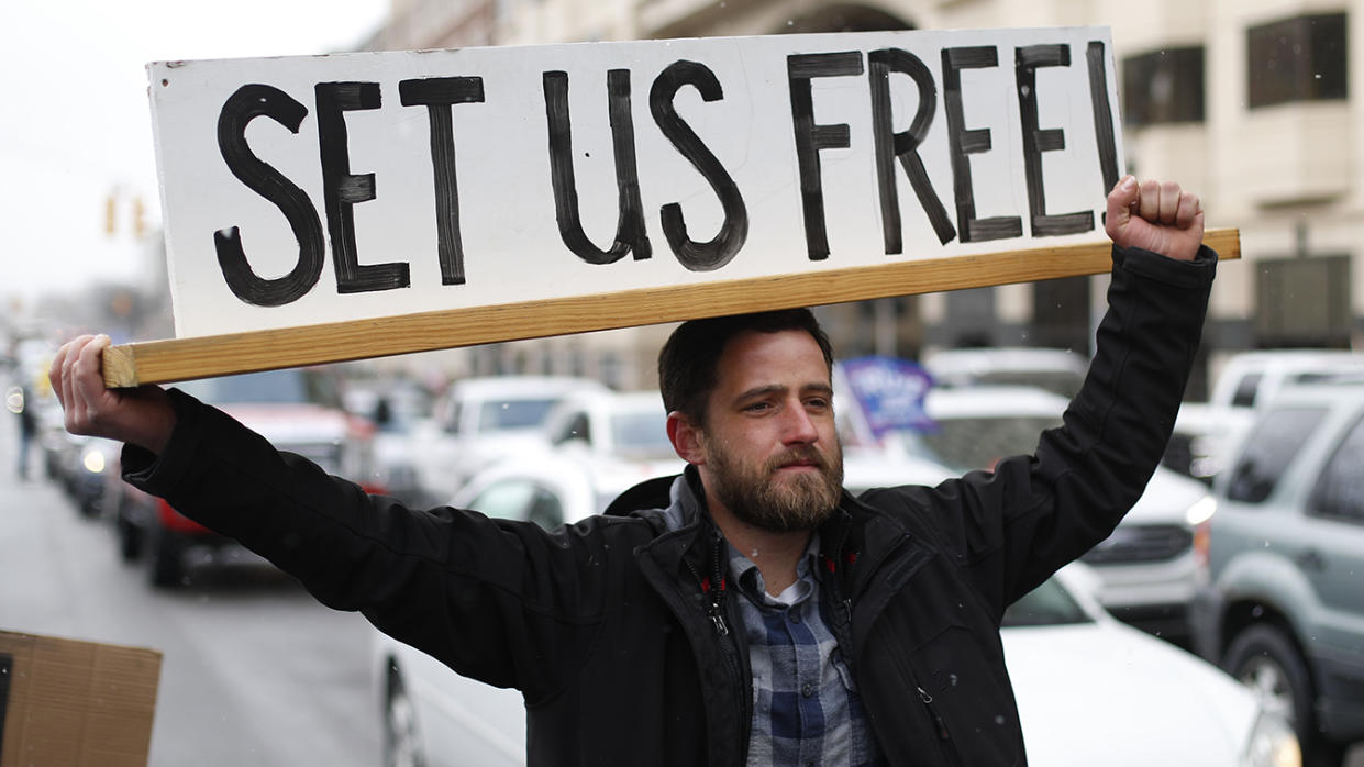 """A man holds a sign reading """"Set us free"""""""