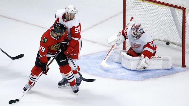 Chicago Blackhawks right wing Ben Smith (28) watches his redirected goal past Detroit Red Wings defenseman Niklas Kronwall, and goalie Jonas Gustavsson during the second period of an NHL preseason hockey game Tuesday, Sept. 17, 2013, in Chicago. (AP Photo/Charles Rex Arbogast)