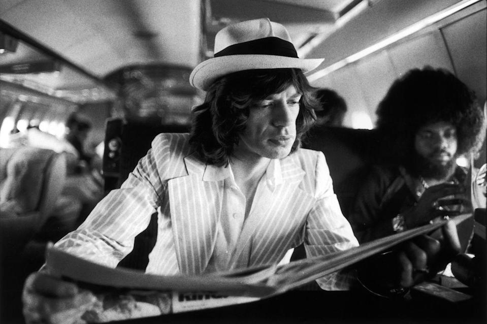 <p>Mick Jagger reads a paper aboard the Rolling Stones' private jet during their 1975 Tour of the Americas. Keyboardist Billy Preston sits behind him. </p>